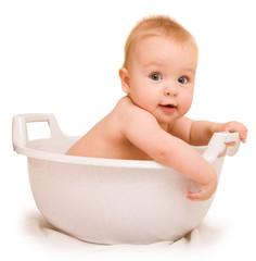 Cute baby having bath in white tub