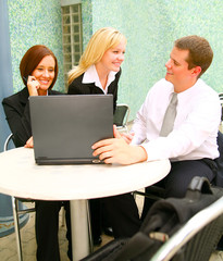 blond business woman chatting with businessman coworker