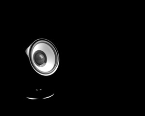 black speaker on pedestal on the black background