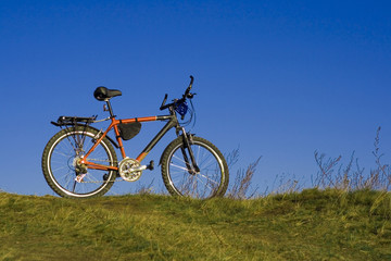 sports bicycle on an autumn meadow against the blue sky