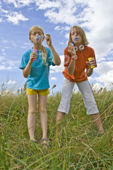 Children blowing bubbles on summer meadow