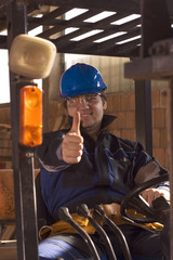 Construction worker handle machine, showing thumb up.
