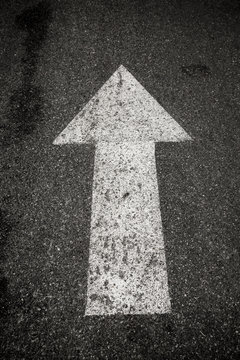 A close up on an arrow on pavement.