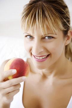happy female ating peach