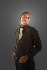 A nice young black man in a suit with yellow tie on a grey