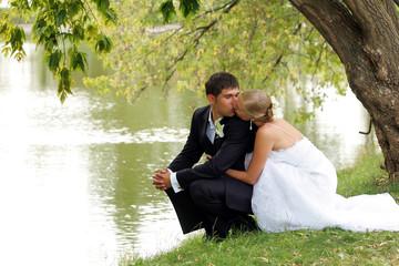 Newlywed couple kissingby lake in romantic scene.