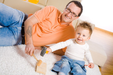 Father and little boy playing together at home.