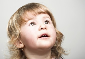 A young, 18 months old girl looks up with wondering eyes.