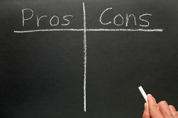 Writing the pros and cons on a blackboard.