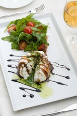 White salad in sauce on a table with a wine glass at restaurant