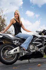 A pretty blonde woman seated on a motorcycle outdoors.