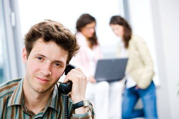 Young businessman receiving phone calls at office