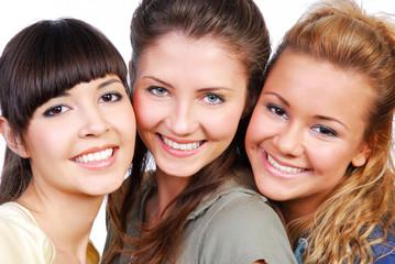 Ñlose-up portrait  of three beautiful girlfriends laughing.