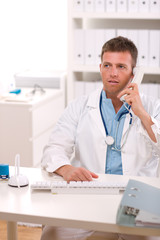 Medical doctor talking on phone at office.