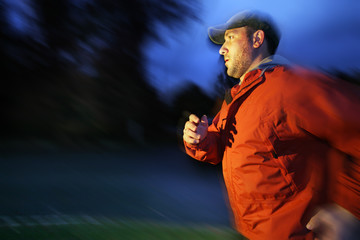 Man running outdoors at twilight, blurred motion.