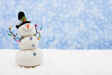 Snowman sitting on snow with snowflake background