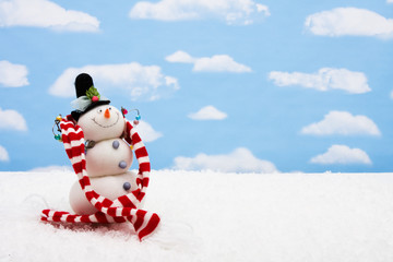 Snowman wearing scarf on sky background, merry Christmas