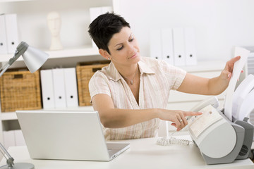 Woman using fax machine at home office.