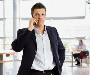 Happy businessman calling on mobile phone.