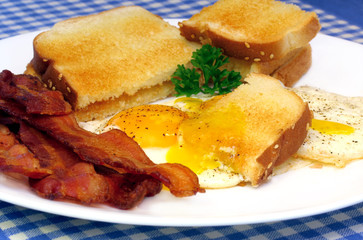 Sunny side eggs, bacon and toast.