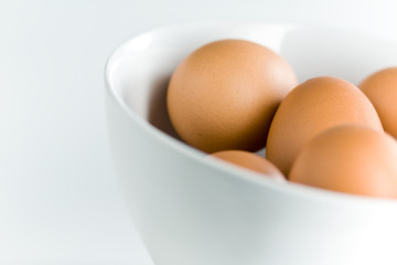 Fresh Brown Eggs in Tilted White Bowl