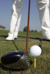 Head of golf club driver is aligned next to golf ball on tee