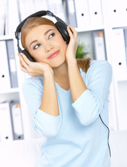 Young woman sitting on couch and listen to the music