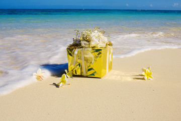 a gift wrapped present on a tropical beach with flowers