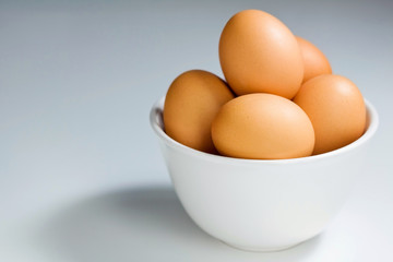 Fresh Brown Eggs In White Bowl on Blue-Grey Background