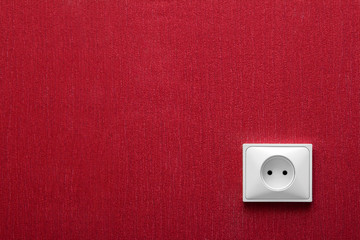 The electric socket in a red wall