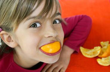 petite fille grimaçant avec son orange