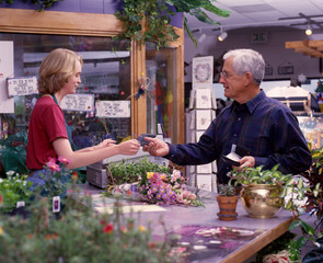 a senior man buys flowers at a plant and garden shop