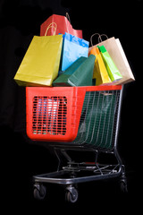 Shopping cart full of gifts on black background