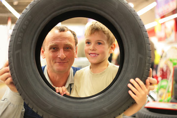 Boy and man look into vehicle tire in store