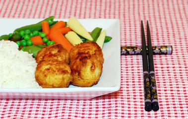 Chicken Balls with rice oriental vegetables and chop sticks