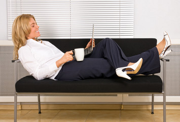 woman relaxing with laptop on couch drinking coffee