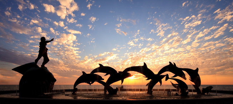 Dolphin statue in front of sunset