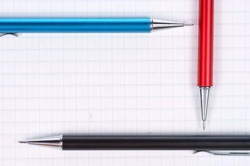 empty page of notebook and black, red, blue pencil