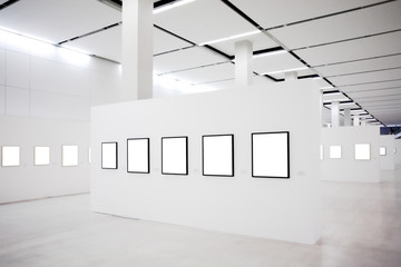 Exhibition with many empty frames on white walls