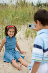 Kids playing with a camera on the beach