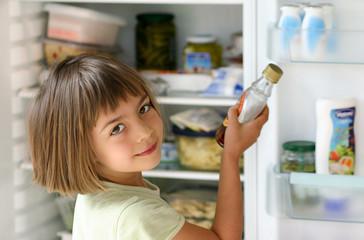enfant se servant du sirop dans le réfrigérateur