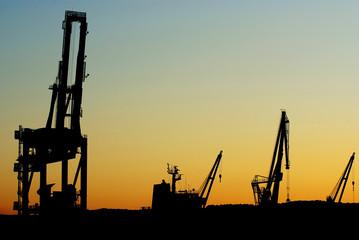 Silhouettes of shipyard cranes