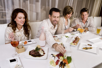 Social group of attractive young couples eating at restaurant