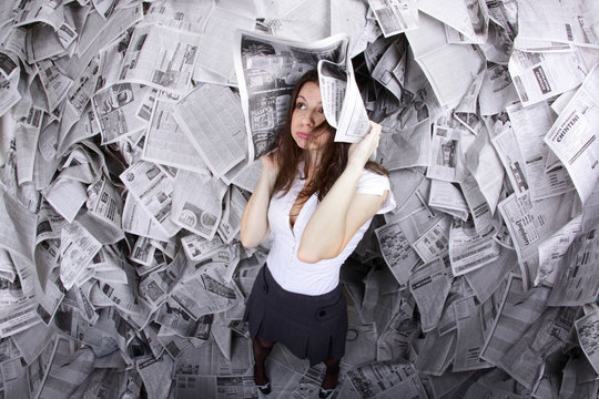 Business woman surrounded by newspapers everywhere