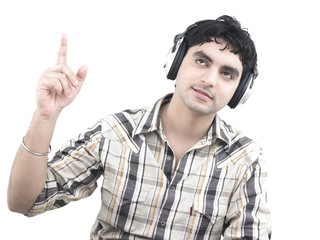 a handsome asian male of indian origin listening to music