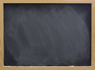 blank blackboard with white chalk dust and smudges
