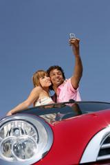 Couple se photographiant dans une voiture décapotable