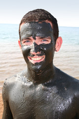 man with mud at the dead sea in Jordan
