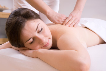 girl getting a back massage in the spa salon