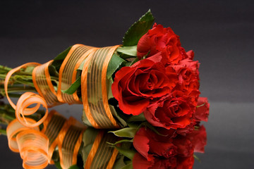 red roses with orange ribbon against the black background